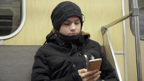 A teenager with a smartphone in his hands is riding in a subway train car Footage