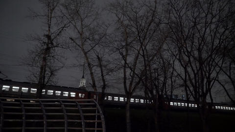 An electric train passes by the station at night Filmmaterial