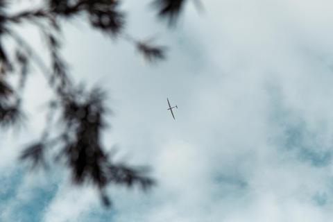 Glider gliding in blue sky from below フォト