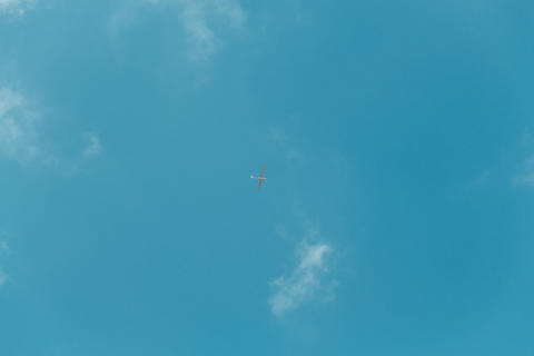 Glider gliding in blue sky from below Foto