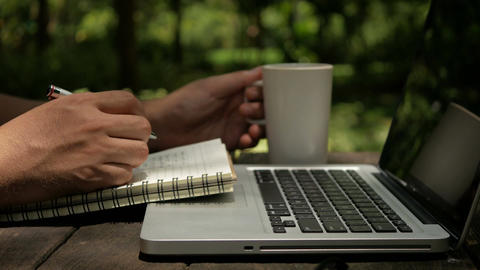 A man freelancer designer use laptop writing on notebook and drinking coffee Footage