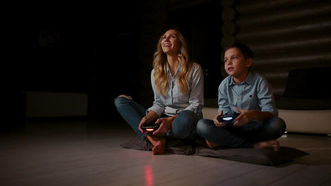 Beautiful mother with her son playing video games on gaming console in the Footage