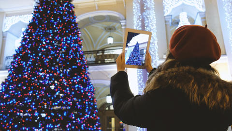 Attractive young girl taking pictures with a tablet Christmas tree Foto
