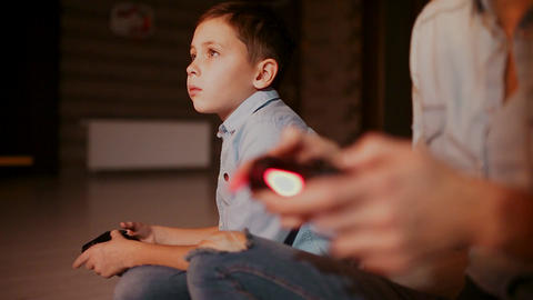 Hands holding a controller to a game console, and in the background the boy Live Action