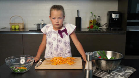 Little girl preparing salad in the kitchen Footage