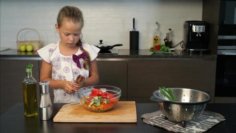 Little girl preparing salad in the kitchen Footage