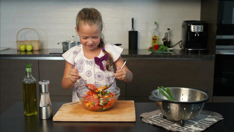 Little girl having fun during preparing salad Footage