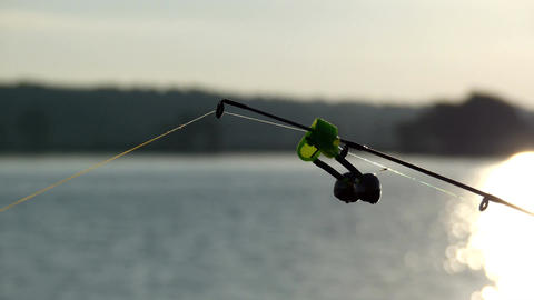Nibble at sunset on the end of the fishing rod with bells on the end Live Action