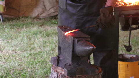 Blacksmith working on metal on anvil at forge Footage