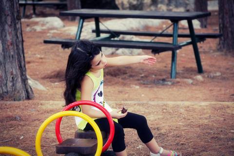 Girl having fun alone on swings in the forest Foto