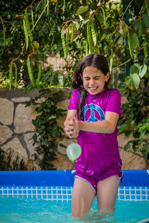Young girl in a bathing suit try to catch water balloon フォト