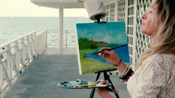 Female artist painting a seascape outdoors Footage