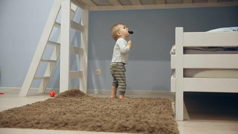 A little boy plays with toys and runs around the camera at home Footage