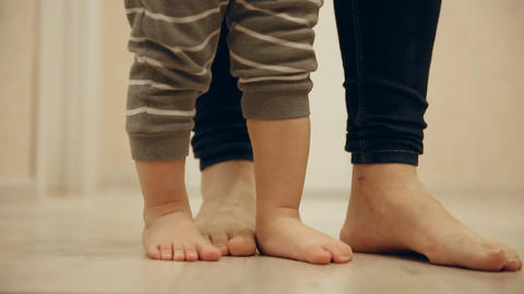 Close-up of feet of mother and baby doing first steps around the house. Feet Footage