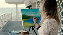 young woman artist painting a seascape standing on the wooden beach terrace Footage