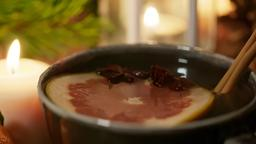 4K Christmas Warming Tea with Cinnamon, Anise and Grapefruit with Festive Candle Photo