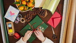4K Top View from Above of Lady's Hands Decorating Christmas Present with Ribbon フォト