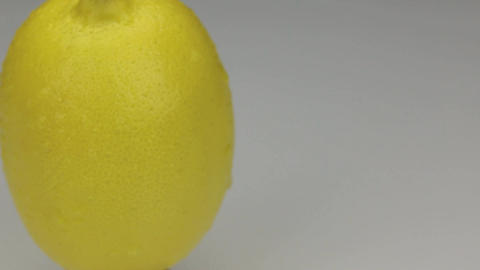 Extreme closeup yellow lemon in drops of dew rotates on its axis Footage