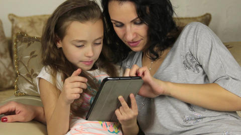 Mother and daughter playing with electronic tablet Footage