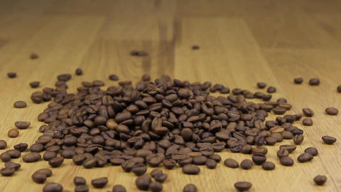 Ð¡offee beans falling on a pile of coffee beans on the wooden background Footage