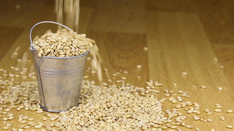 Fall into a bucket of pearl barley grains and on wooden floor Footage