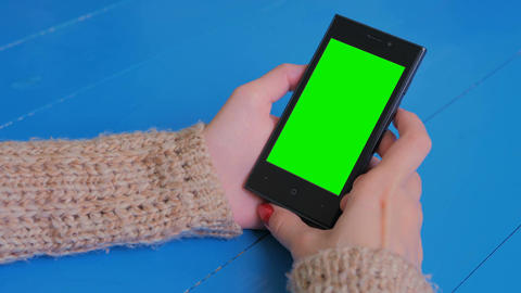 Woman looking at smartphone with green screen Filmmaterial