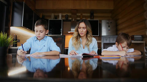 Happy family mother of two children helps the sons to do their homework sitting Archivo