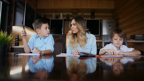 Happy family mother of two children helps the sons to do their homework sitting Footage
