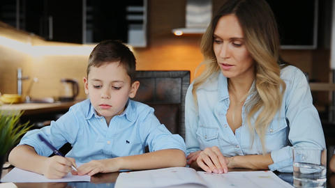 Smiling mother helping his son doing homework, dictates the text to help you Live Action