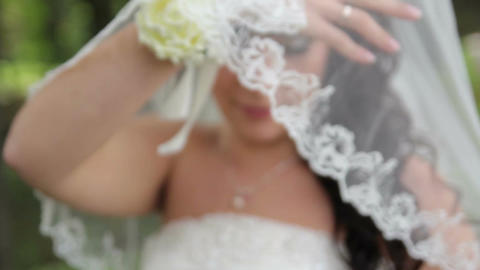 Beautiful bride with a wedding bouquet opens the veil Live Action