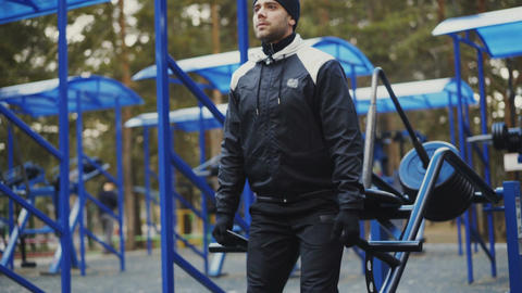 Attractive athlete man doing exercise at outdoor gym in winter park Footage