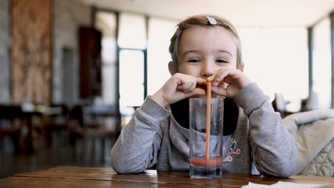 Little girl drinking from a glass of juice through a straw in a cafe Footage