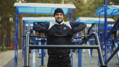 Young athlete man doing exercise at outdoor gym in winter park Footage