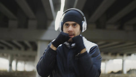 Close-up tracking shot of sportive man boxer in headphones doing boxing exercise Live Action