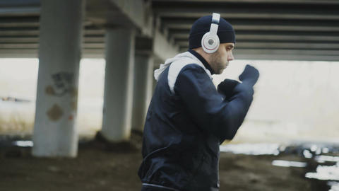 Tracking shot of sportive man boxer in headphones doing boxing exercise in urban Live Action