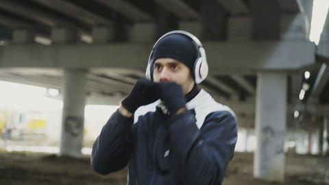 Dolly shot of sportive man boxer in headphones training punches in urban Live Action