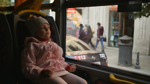 Little Blonde Girl in a pink jacket, Kid is Sitting in a Bus Cabin. Sitting on Bild