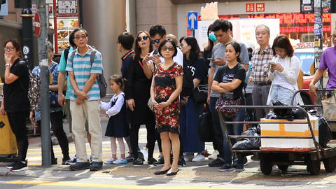 Asian people waiting at crosswalk on busy street ビデオ