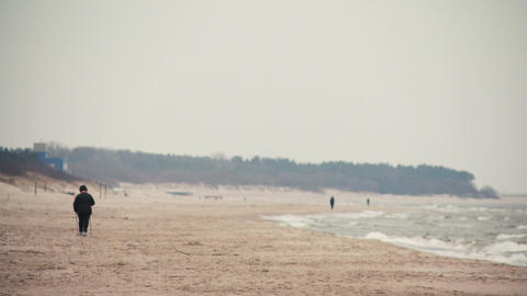 Person recreation nordic walking on the beach in Palanga, Lithuania Live Action
