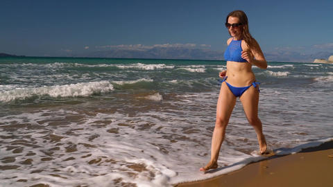Beach bikini woman carefree running along the water on the beach. Picturesque ビデオ