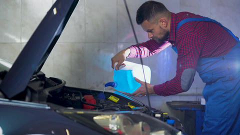 Car service, repair, maintenance and people concept - auto mechanic working at Footage