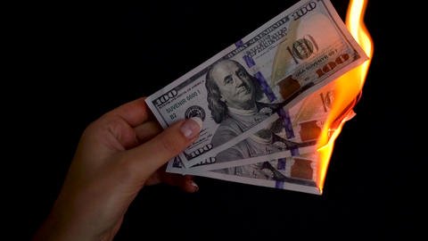 Burning dollars in a hand close-up on a black background. Slow motion Footage
