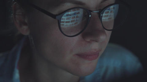 Woman in glasses looking on the monitor and surfing Internet Footage