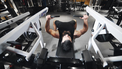 Strong man is pumping muscles at the gym, strength exercises on simulators Live Action