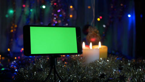 Smartphone with a green screen, on a New Year's background. Movement of the Bild