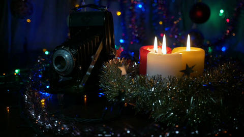 Three New Year's candles and an old camera. Movement of the camera around the Live Action