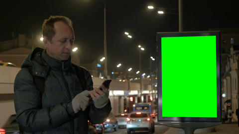 A man is talking on the phone at night in the city. A smartphone is a means of Footage