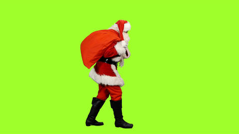 Side view of Santa carrying gifts in sack on green background, chroma key Footage