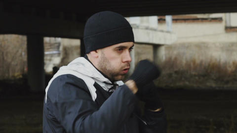 Slowmotion of sportive man boxer doing boxing exercise in urban location Live Action