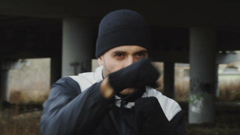 Slowmotion of concentrated man boxer doing boxing exercise in urban location Footage